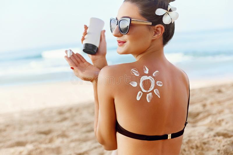 Skin care. Sun protection. Woman apply sun cream. Girl Holding Moisturizing Sunblock. Woman With Suntan Lotion On Beach In Form Of royalty free stock images