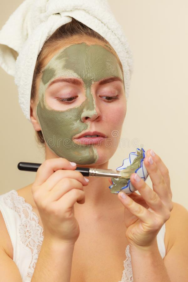 Woman applying with brush clay mud mask to her face stock image