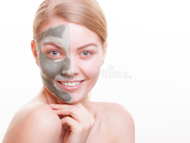 Skin care. Woman applying clay mask on face. Spa. Skin care. Young woman applying clay mask on her face. Girl taking care of her dry compexion. Isolated. Spa stock photo
