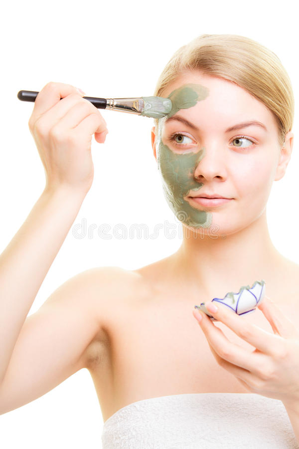Skin care. Woman applying clay mud mask on face. Skin care. Woman applying with brush clay mud mask on face isolated. Girl taking care of dry complexion. Beauty stock images