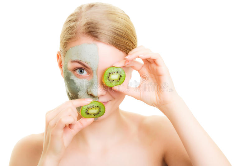 Skin care. Woman in clay mask with kiwi on face. Skin care. Woman in clay mud mask on face covering mouth and eye with slices of kiwi isolated. Girl taking care royalty free stock image