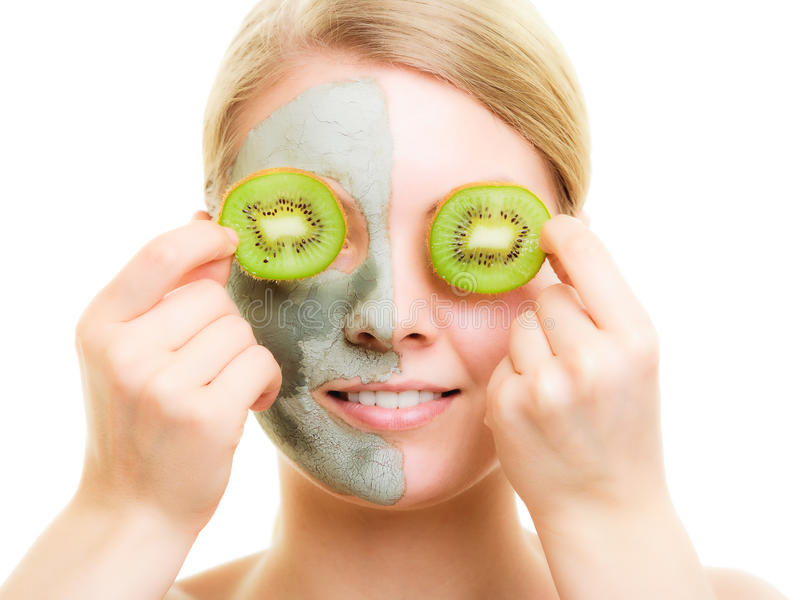 Skin care. Woman in clay mask with kiwi on face. Skin care. Woman in clay mud mask with kiwi fruit on face isolated. Girl taking care of dry complexion royalty free stock image