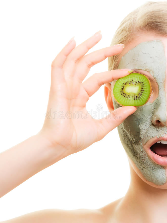 Skin care. Woman in clay mask with kiwi on face. Skin care. Surprised woman in clay mud mask with kiwi fruit on face isolated. Girl taking care of dry complexion stock photography