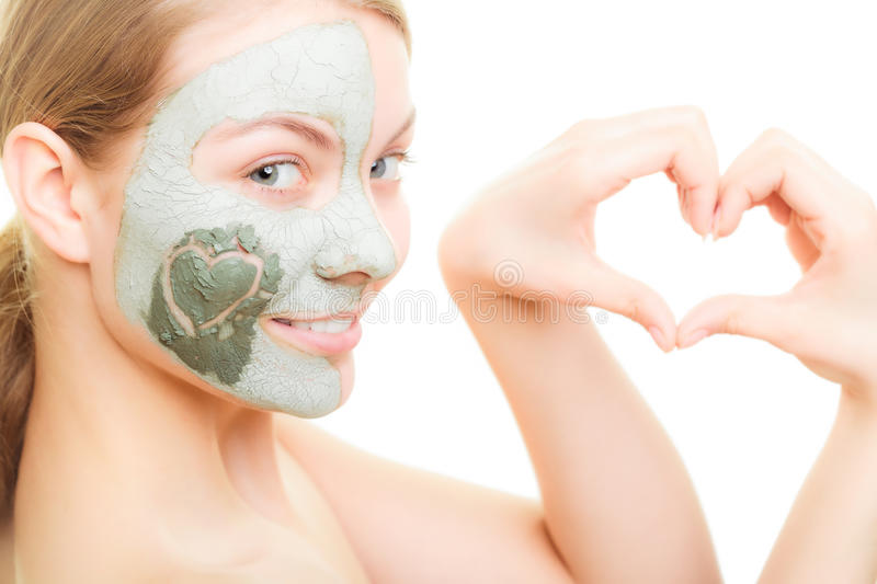 Skin care. Woman in clay mud mask on face. Beauty. Skin care. Woman in clay mud mask on face with heart on cheek isolated on white. Girl showing symbol of love stock image