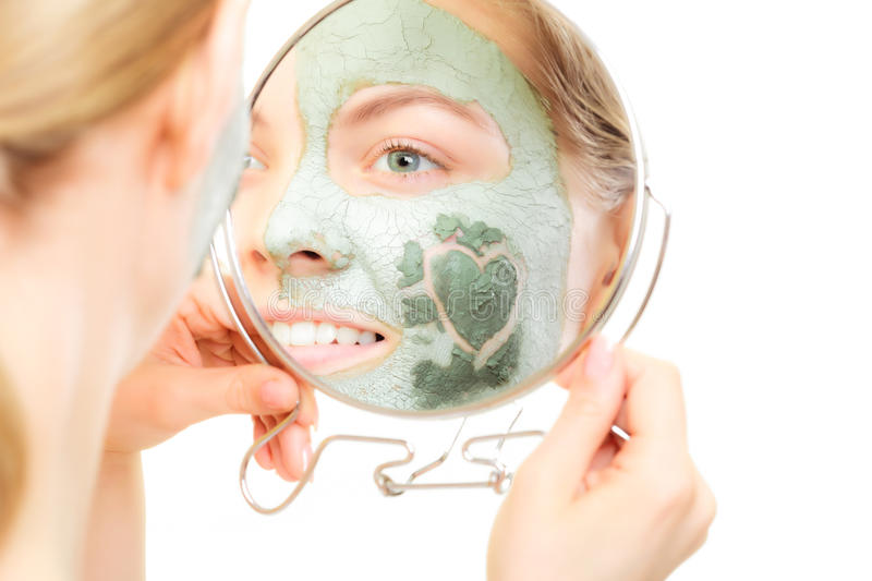 Skin care. Woman in clay mud mask on face. Beauty. Skin care. Woman in clay mud mask on face with heart on cheek looking in the mirror isolated on white. Girl stock photography