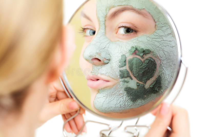 Skin care. Woman in clay mud mask on face. Beauty. Skin care. Woman in clay mud mask on face with heart on cheek looking in the mirror isolated on white. Girl stock photo