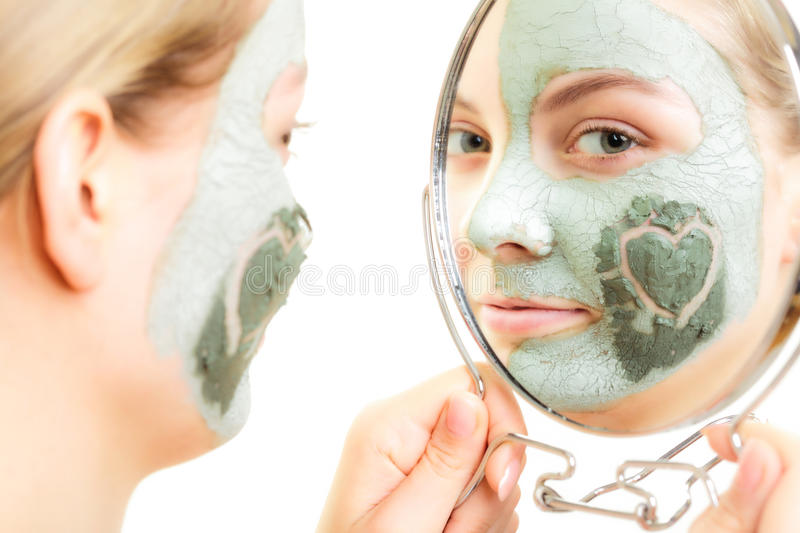 Skin care. Woman in clay mud mask on face. Beauty. Skin care. Woman in clay mud mask on face with heart on cheek looking in the mirror isolated on white. Girl stock image