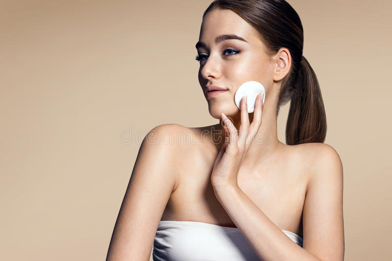 Skin care woman removing face makeup - skin care concept. Photos of appealing brunette girl on beige background stock photos
