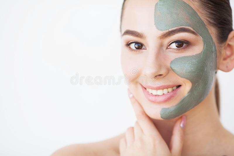 Skin Care. Young woman with cosmetic clay mask holding cucumber royalty free stock images