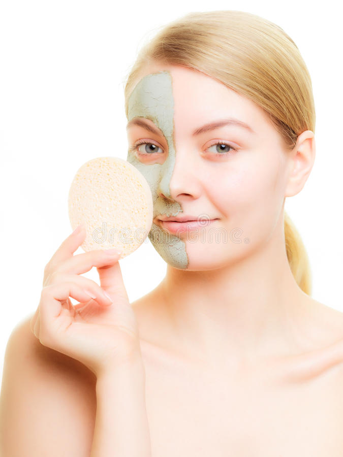 Skin care. Young woman removing clay mud mask isolated on white. Girl taking care of dry complexion royalty free stock photography