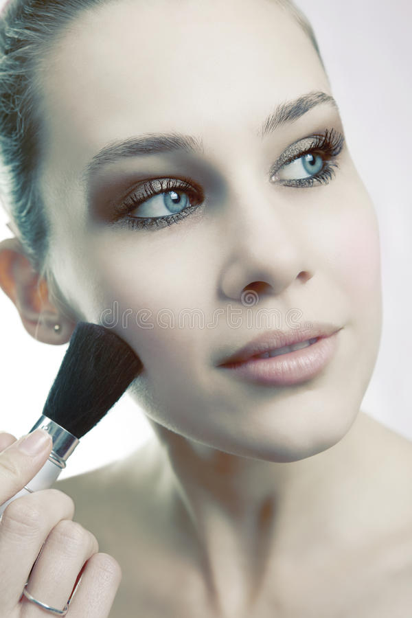 Skin cosmetics - woman using brush on her face. Skin cosmetics - sensual woman using brush on her face stock photography