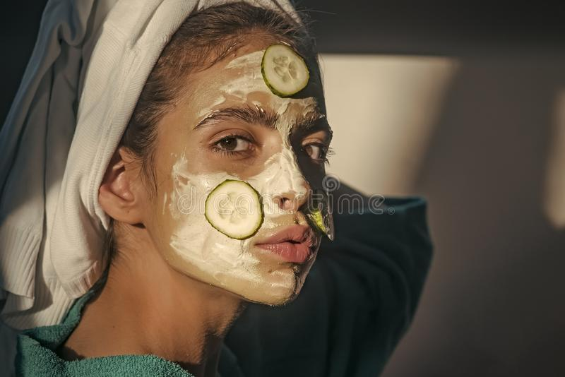 Skin and hair care, spa, wellness. Girl or woman face with cucumber mask, towel on head. Cosmetics, cosmetology, dermatology. Rejuvenation, health, youth stock photo