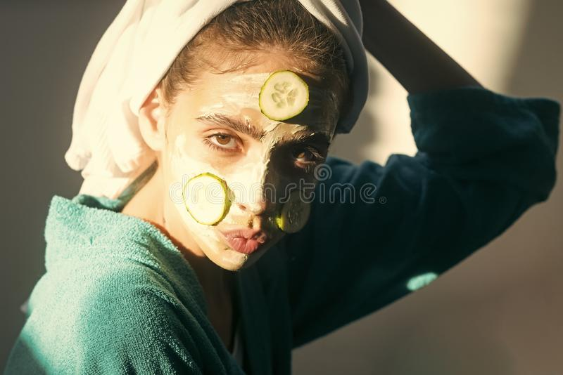 Skin and hair care, spa, wellness. Girl or woman face with cucumber mask, towel on head. Rejuvenation, health, youth. Cosmetics, cosmetology, dermatology stock images