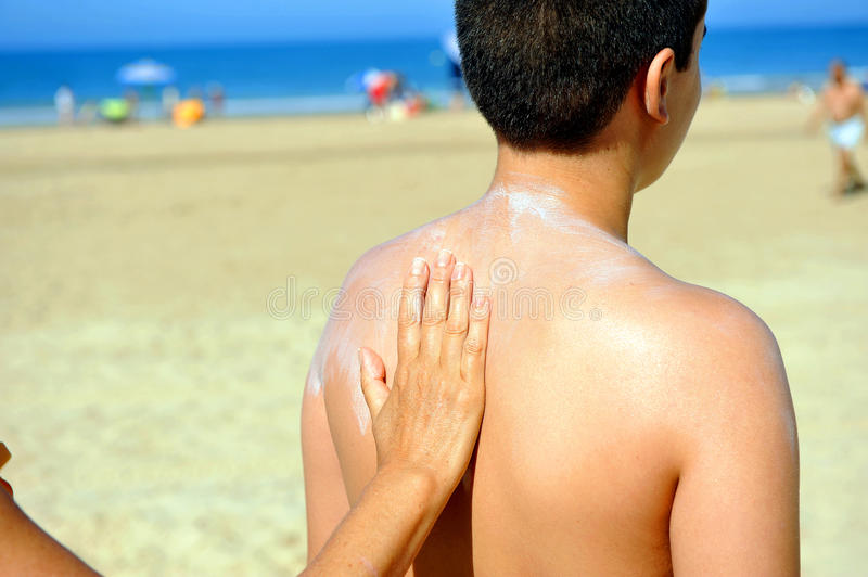 Skin protection at the beach with sunscreen royalty free stock image