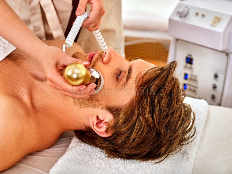 Skin resurfacing procedure facial procedure on ultrasound face machine. Male acne treatment. Man receiving electric lift massage at spa salon. Forced rest in stock image