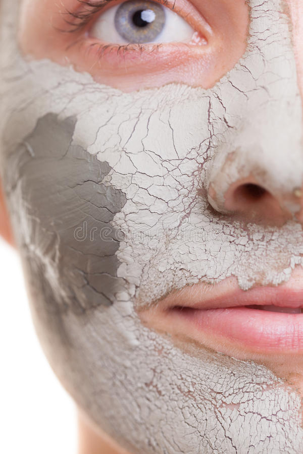 Skin. Woman applying clay mask on face. Spa. Skin care. Closeup of female face. Young woman applying clay mask. Girl taking care of her dry compexion. Isolated stock photography