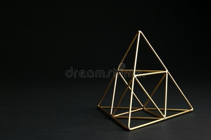 Skinande dekorativ guld- pyramid på svart bakgrund royaltyfri bild