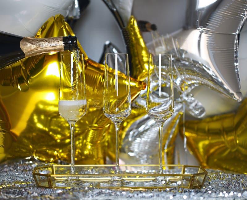 Skinande exponeringsglas av champagne över svart, vit, guld- och silverballongbakgrund arkivbild