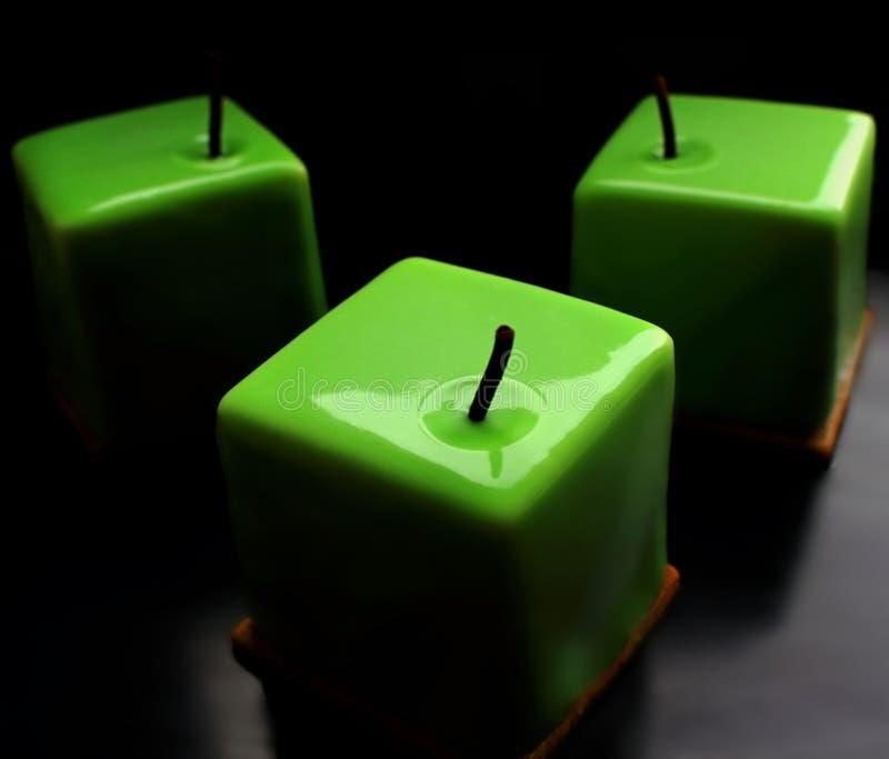 Skinande glasade kubefterrätter för grönt äpple på svart bakgrund arkivbild