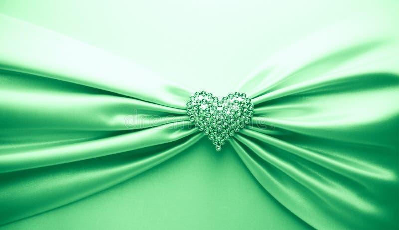 Skinande grönt satängband och diamanthjärta arkivfoto