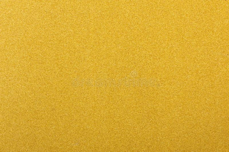 Skinande gul bakgrund för textur för guld- folie för blad arkivbild