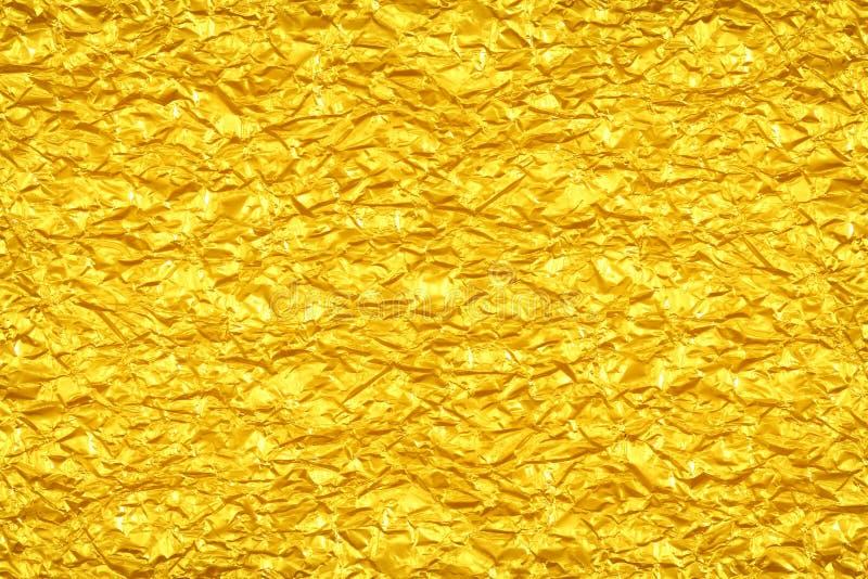 Skinande gul bakgrund för textur för guld- folie för blad royaltyfri bild