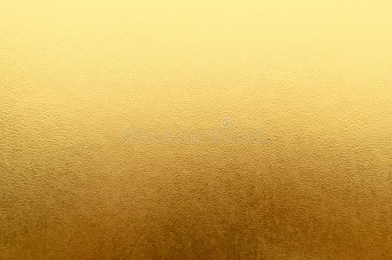 Skinande gul metallisk bakgrund för bladguldfolietextur arkivfoto