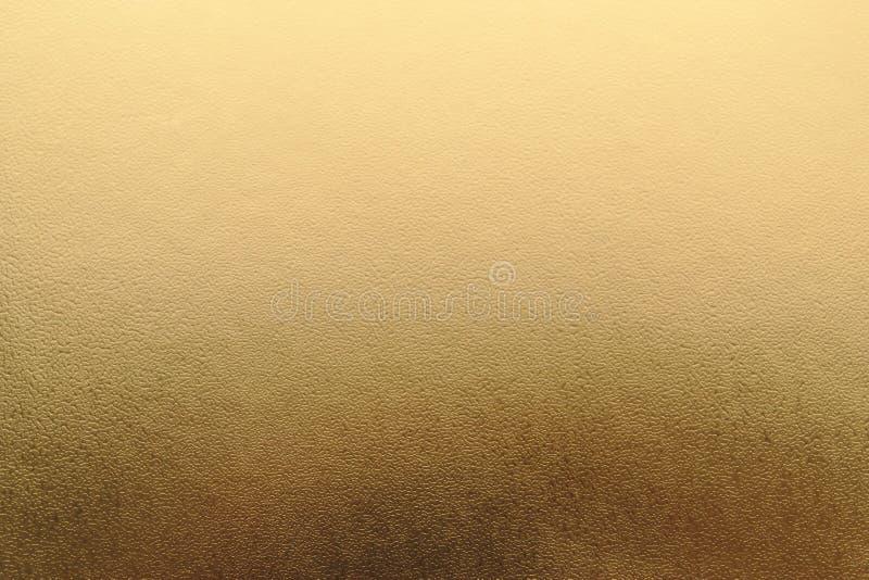 Skinande gul metallisk bakgrund för bladguldfolietextur arkivbilder