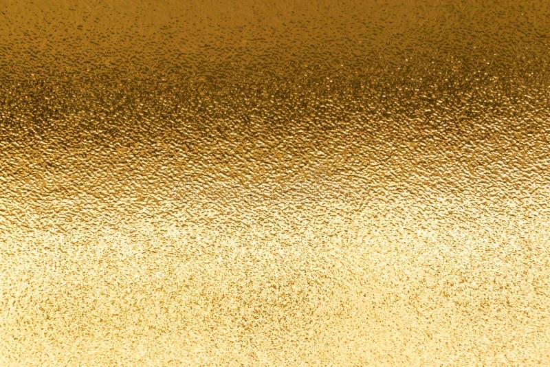 Skinande gul metallisk bakgrund för bladguldfolietextur royaltyfri foto
