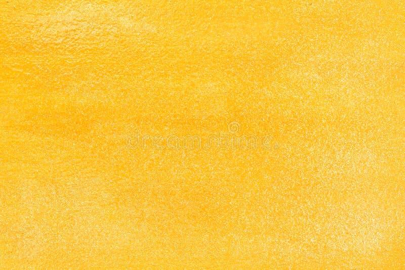 Skinande guld- betongväggabstrakt begrepp, färgrik textur blänker modeller för bakgrund arkivbild