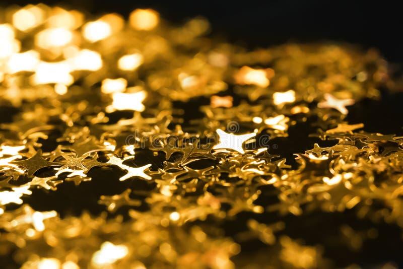 Skinande guld- paljetter på mörk bakgrund, closeup arkivbild