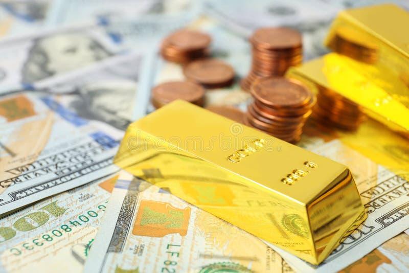 Skinande guld- stänger och mynt på dollar royaltyfri fotografi