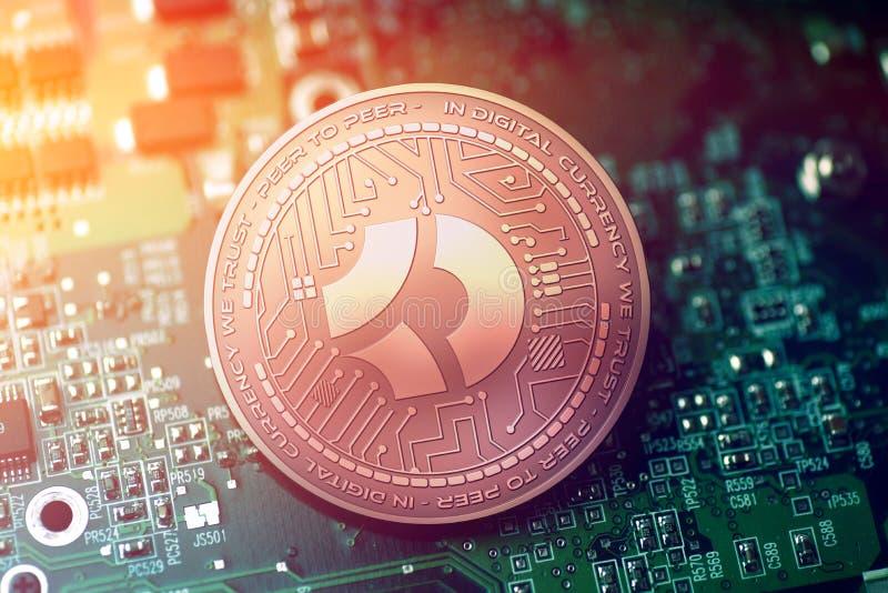 Skinande MÖRKT cryptocurrencymynt för koppar BITCOIN på oskarp moderkortbakgrund fotografering för bildbyråer