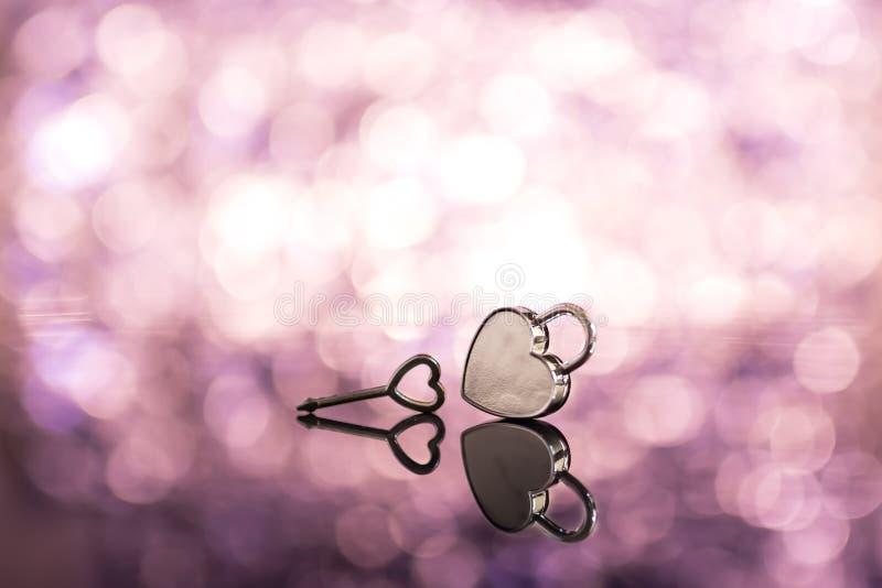 Skinande metallhjärtalås och tangent i rosa ljus- och bokehbackgroun arkivfoto