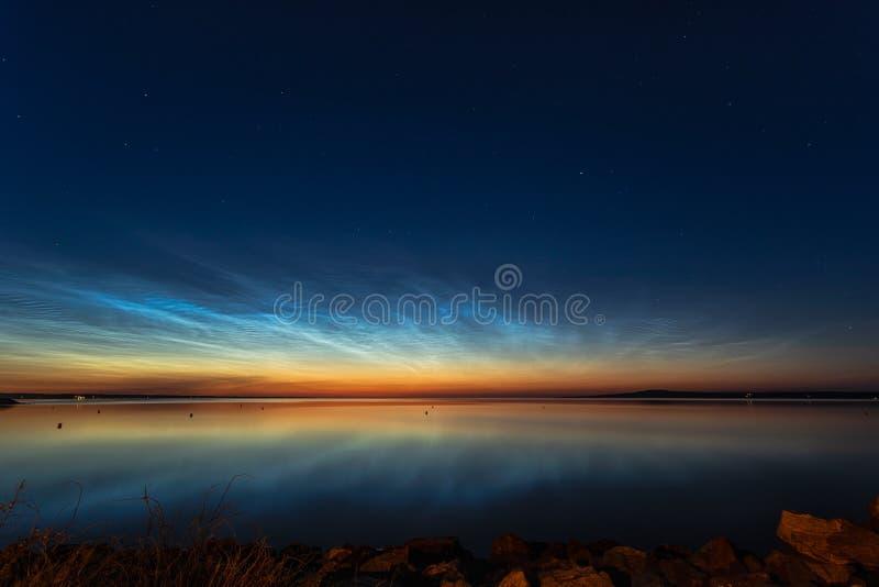 Skinande moln för natt över sjön arkivfoton