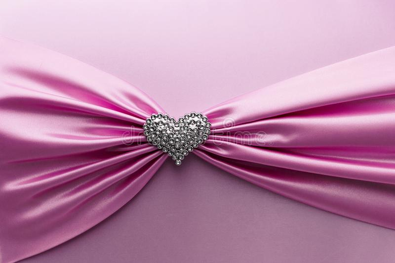 Skinande rosa satängband och diamanthjärta arkivfoto