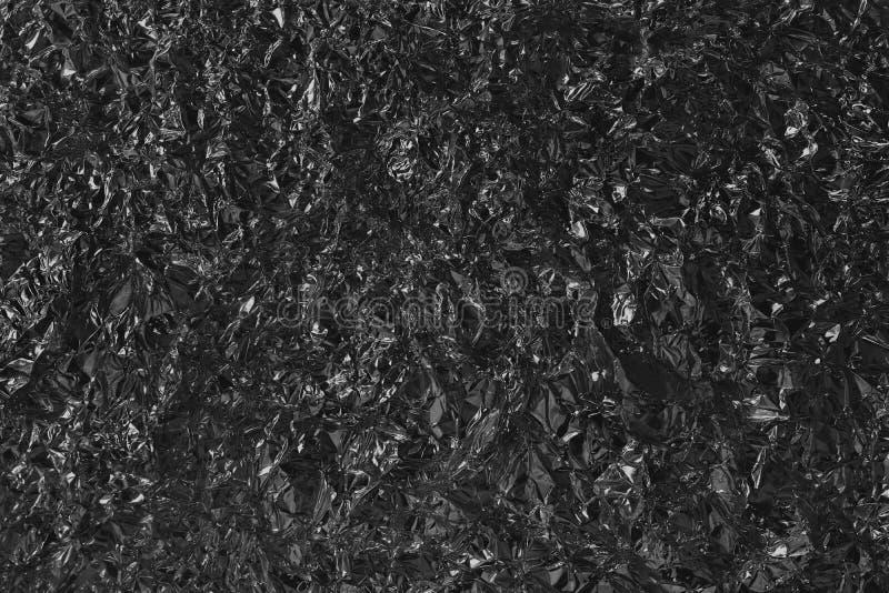 Skinande svart grå foliemetalltextur, abstrakt inpackningspapper med hög upplösning för bakgrund royaltyfri foto