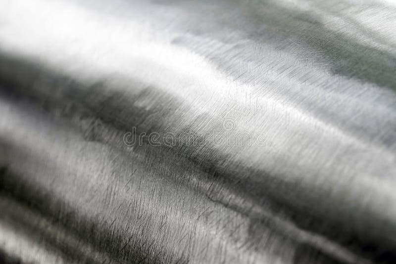 Skinande yttersida och skrapat på rostfritt stål arkivfoton