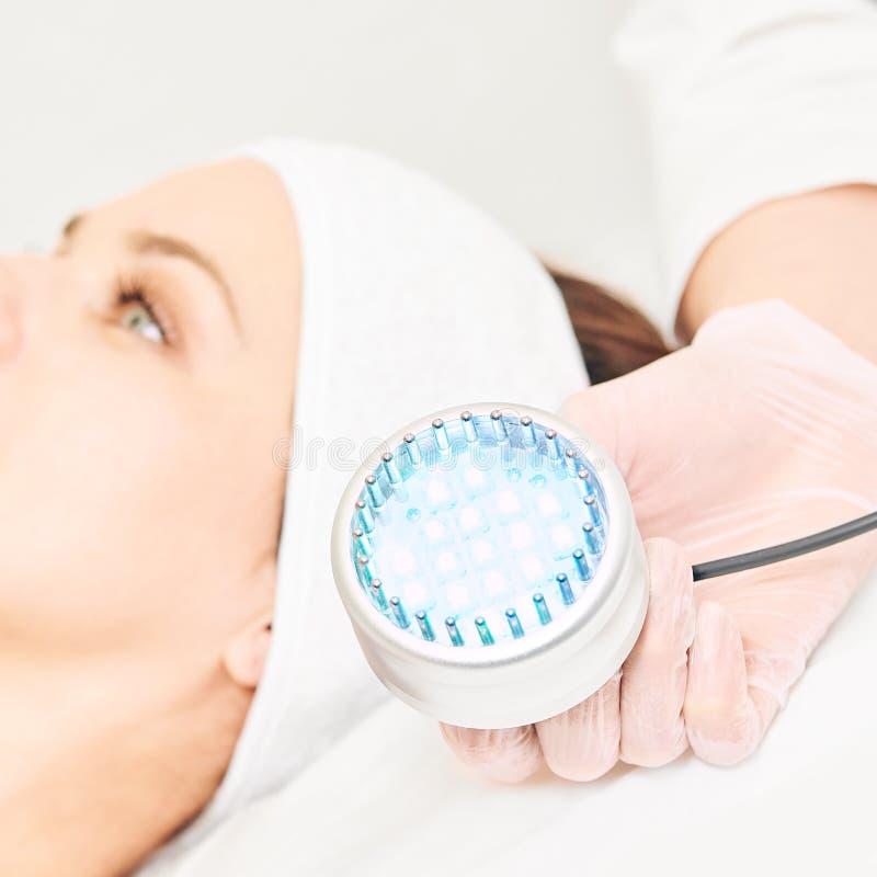 Skincare整容术面部做法 秀丽妇女面孔 蓝色轻的医疗疗法 专家手 免版税图库摄影