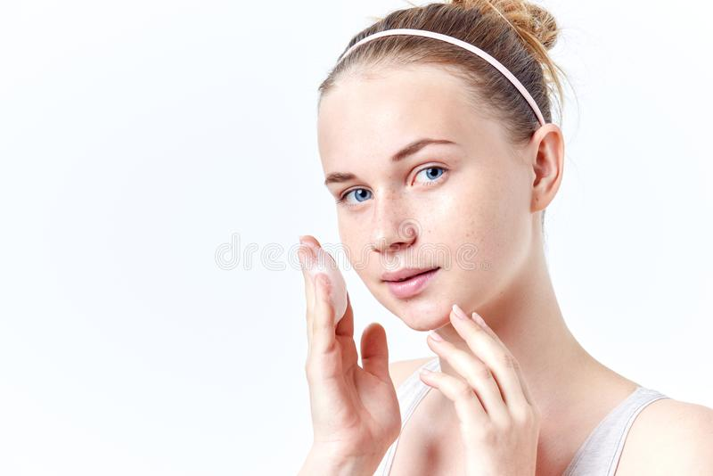 Skincare подростка Усмехаясь красивая предназначенная для подростков девушка с веснушками и голубыми глазами используя пенясь cle стоковая фотография rf