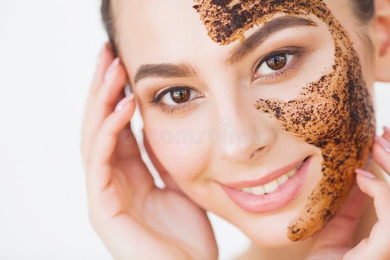 ??skincare 年轻迷人的女孩在她的面孔做一个黑木炭面具 免版税图库摄影