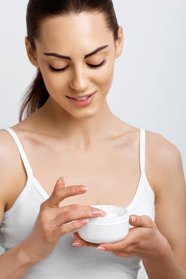 ??skincare 有健康光滑的面部干净的皮肤藏品瓶奶油的妇女 秀丽面孔关心 r r 免版税库存图片