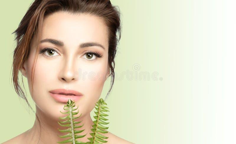 ??Skincare 秀丽有新鲜的绿色叶子的温泉妇女 健康和温泉治疗概念 免版税库存照片