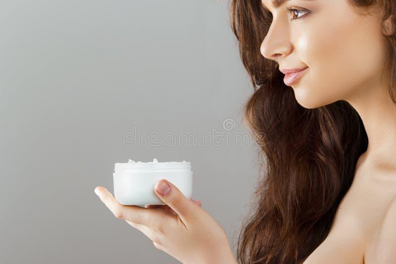 Skincare 被设色的背景秀丽蓝色概念容器装饰性的深度详细资料域充分的仿效宏观自然超出珍珠浅天空 拿着化妆奶油的年轻俏丽的妇女 软的皮肤和赤裸肩膀,与轻的裸体构成的模型, 库存图片