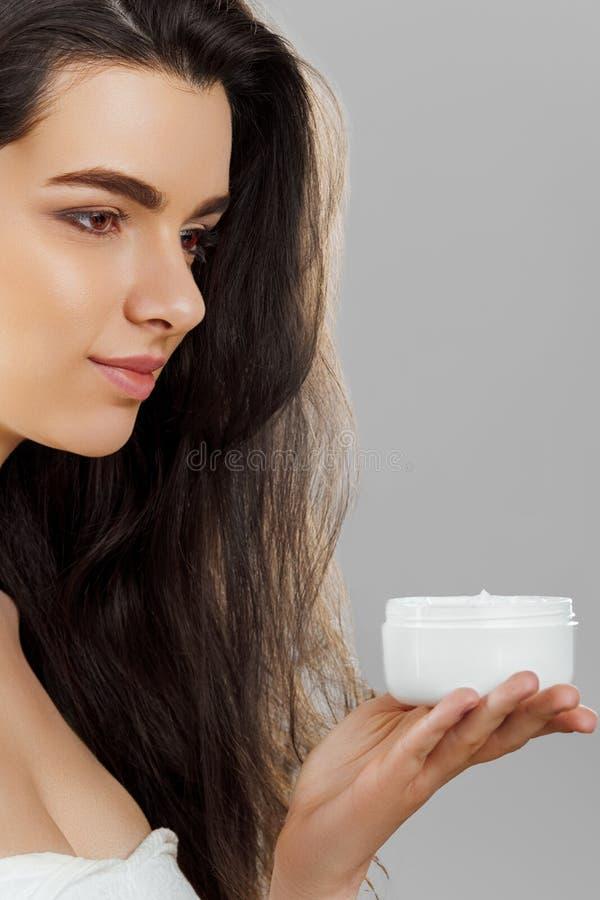 Skincare 被设色的背景秀丽蓝色概念容器装饰性的深度详细资料域充分的仿效宏观自然超出珍珠浅天空 拿着化妆奶油的年轻俏丽的妇女 软的皮肤和赤裸肩膀,与轻的裸体构成的模型, 库存照片
