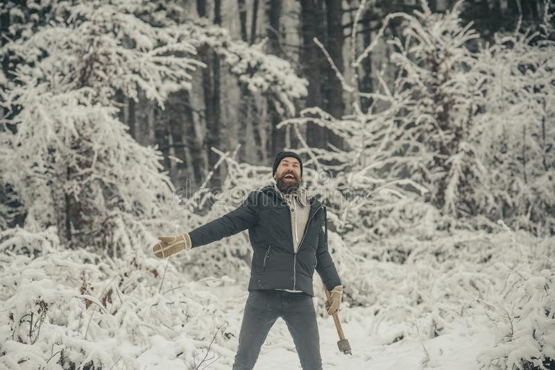 Skincare and beard care in winter, beard warm in winter. Bearded man with axe in snowy forest. Man lumberjack with ax. Temperature, freezing, cold snap stock image