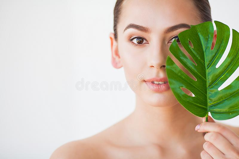 Skincare. Beautiful Woman Portrait on White Background With Clean Skin and Green Leaf in Hand.  stock photo