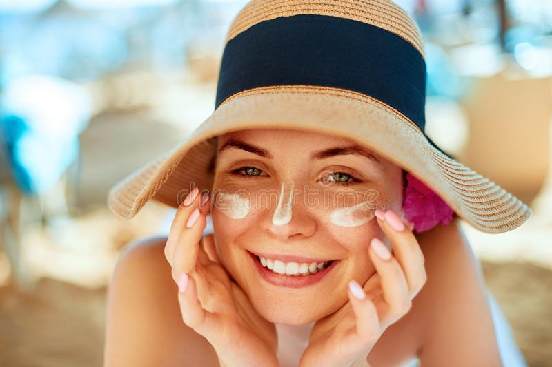 Skincare. Beauty Concept. Young pretty woman applying sun cream and touch own face. Female in hat smear sunscreen lotion on skin. royalty free stock image