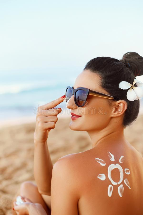 Skincare. Beauty Concept. Young pretty woman applying suncream  and touch own face. Female i smear  sunscreen lotion on skin. royalty free stock photography