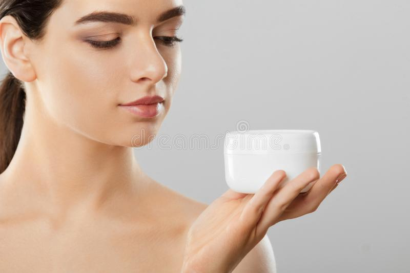 Skincare. Beauty Concept. Young pretty woman holding cosmetic cream. Soft skin and naked shoulders,model with light nude make-up, stock image
